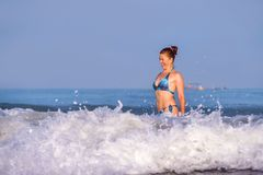 Young happy and playful red hair woman in bikini swimming on the sea playing with big waves enjoying Summer holidays paradise. Beach relaxed and excited in royalty free stock photo