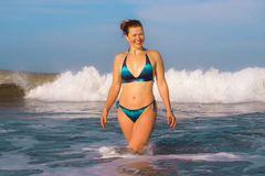 Young happy and playful red hair woman in bikini swimming on the sea playing with big waves enjoying Summer holidays paradise. Beach relaxed and excited in royalty free stock images
