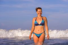 Young happy and playful red hair woman in bikini swimming on the sea playing with big waves enjoying Summer holidays paradise. Beach relaxed and excited in stock photography