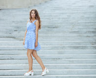 Young happy playful woman in light striped white blue dress posing at concrete stairway outdoor. Young happy playful lady in light striped white blue dress Stock Photos