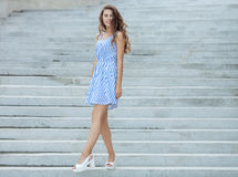 Young happy playful woman in light striped white blue dress posing at concrete stairway outdoor. Young happy playful lady in light striped white blue dress Stock Photo