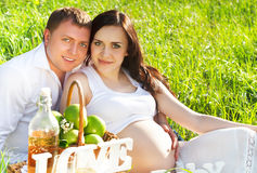 Young happy pregnant couple in the flowering spring park Royalty Free Stock Photo