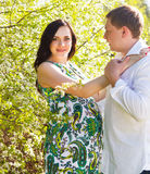 Young happy pregnant couple in the flowering spring park Royalty Free Stock Images