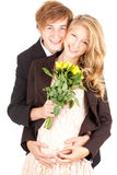 Young happy pregnant couple with flowers Stock Photos