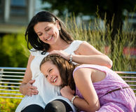 Young happy pregnant mom caressing her kid girl Royalty Free Stock Image