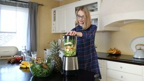 Young happy pregnant woman preparing smoothie in blender stock video footage