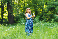 Young happy pregnant woman relaxing and enjoying life in nature. Outdoor shot. Copyspace Royalty Free Stock Image