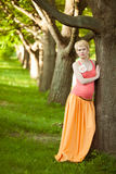 Young happy pregnant woman relaxing in nature Royalty Free Stock Photo