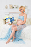Young happy pregnant woman sitting on couch in blue lace kit Stock Images