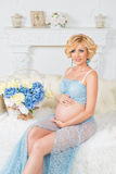 Young happy pregnant woman sitting on couch in blue lace kit Royalty Free Stock Photo
