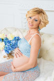 Young happy pregnant woman sitting on couch in blue lace kit Royalty Free Stock Photos