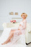 Young happy pregnant woman sitting on sofa in white lace dressing gown. Stock Photography