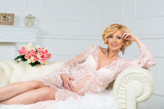 Young happy pregnant woman sitting on sofa in white lace dressing gown. Royalty Free Stock Photos