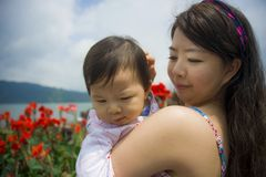 Young happy and pretty Asian Korean woman as loving mother holding adorable daughter baby girl during holidays excursion with lake stock photos