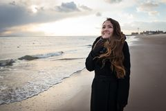 Young happy pretty woman in elegant clothes on the winter beach in NYC. Dreaming and smiling. One person. Winter season. Brighton Beach stock photography