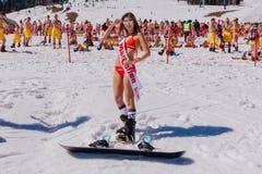 Young Happy Pretty Women On A Snowboard In Colorful Bikini. Stock Photos