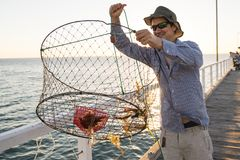 Proud attractive fisherman showing fish and crabs basket net captures smiling at sea dock sunset in man fishing as weekend hobby. Young happy and proud royalty free stock images