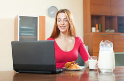Young happy red-haired girl in pink using laptop during breakfas Stock Photography