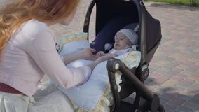 Young happy redhead mother speaking with baby in carriage and smiling and taking care of him on a nice spring day. Happy young redhead mother speaking with baby stock footage