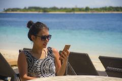 Relaxed Asian Chinese woman using internet social media on mobil. Young happy and relaxed Asian Chinese woman using internet social media on mobile phone sending Royalty Free Stock Photos