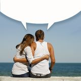 Young happy romantic couple at sea coast with dialogue box above them Stock Photos