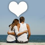 Young happy romantic couple at sea coast with dialogue box above them Royalty Free Stock Photos