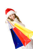 Young happy Santa Claus woman with shopping bags. Young attractive smiling Santa Claus woman holding shopping bags. Isolated on white Stock Images