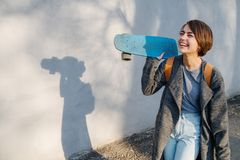Young happy short-haired brunette woman with skate in hands in front of a wall royalty free stock photo