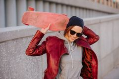 Young happy short-haired light brunette woman with skateboard in hands stock images