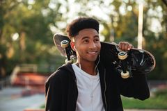 Young happy skateboarder man holding skateboard. On his shoulders at public park Royalty Free Stock Photography