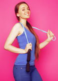 Young happy slim girl with skipping rope on pink background smil Royalty Free Stock Photography