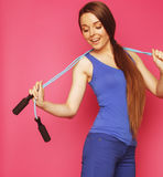 Young happy slim girl with skipping rope on pink Royalty Free Stock Photo