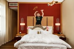 Young happy small Caucasian girl fooling jumping in the air with her toys above the bed in bedroom royalty free stock photo