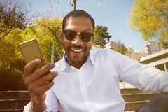 Young happy smiling african american male in sun glasses using mobile smartphone in city garden park. Young happy smiling african american male in sun glasses Royalty Free Stock Image