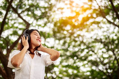 Young happy smiling asian woman listening music with headphones Stock Photo