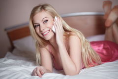 Young happy smiling beautiful girl lying on bed Stock Photography