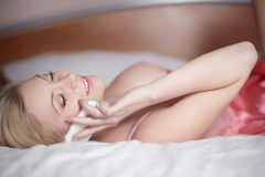 Young happy smiling beautiful girl lying on bed Stock Photo