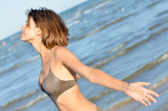 Young happy smiling beautiful woman enjoying sea on sandy beach Stock Photo