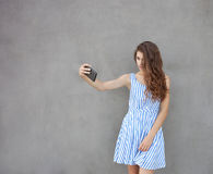 Young happy smiling beautiful woman in light dress with long brunette curly hair posing against wall on a warm Stock Photo