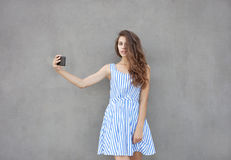 Young happy smiling beautiful woman in light dress with long brunette curly hair posing against wall on a warm Stock Images