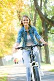 Young happy smiling blonde beautiful woman wearing in white jeans riding bikes in park bright sunlight on summer day stock photo