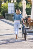 Young happy smiling blonde beautiful woman wearing in white jeans riding bikes in park bright sunlight on summer day royalty free stock photo