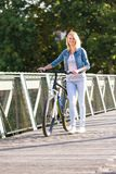 Young happy smiling blonde beautiful woman wearing in white jeans riding bikes in park bright sunlight on summer day royalty free stock photography