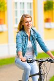 Young happy smiling blonde beautiful woman wearing in white jeans riding bikes in park bright sunlight on summer day stock image