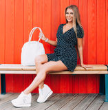 Young happy smiling blonde tan woman posing outdoor in summer time wearing vintage dress, sitting at wooden bench at red backgroun stock images