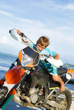 Young Happy Smiling Boy Riding Motorbike On Royalty Free Stock Image