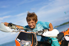 Young happy smiling boy riding motorbike on Stock Photos