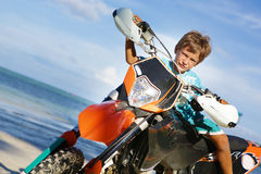 Young happy smiling boy riding motorbike on Royalty Free Stock Photography