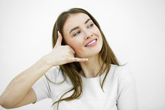 Young happy smiling brunette woman with call me gesture Royalty Free Stock Images