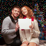 Young happy smiling casual couple holding sign Stock Images